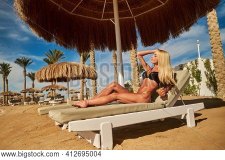 Sexy Woman Wearing Bikini Sitting On Lounger Under Straw Canopy Umbrella At The Beach Holding Glass
