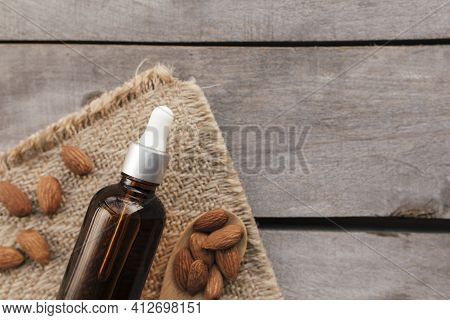 Almond Essential Oil In Glass Bottle With Spoon. Cosmetic Concept On Wooden Background With Sackclot