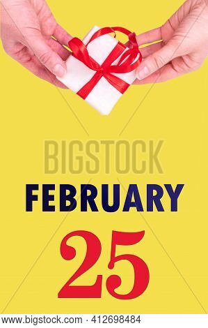 February 25th. Festive Vertical Calendar With Hands Holding White Gift Box With Red Ribbon And Calendar Date On Illuminating Yellow Background. Winter month, day of the year concept.
