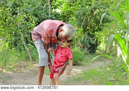 Elderly Grandfather Of Indian Origin Lovingly Holding Little Younger Grandson, India. Concept For Ch