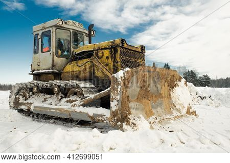 Yellow Crawler Tractor Bulldozer With A Bucket Works In Winter Clearing The Road From Snow. Frosty D