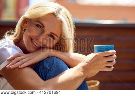 Happy Middle Aged Caucasian Woman With Cup Of Coffee