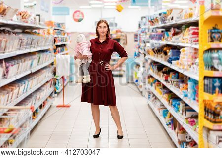 Shopping And Consumerism. A Young Caucasian Mother Holding Her Baby In Her Arms And Posing At Aisle