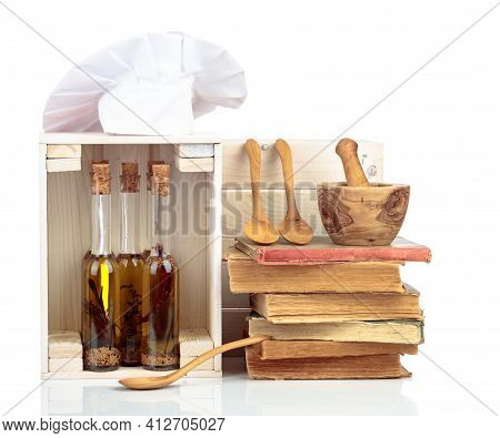 Chef's Hat, Vintage Cookbooks, And Bottles Of Aromatized Olive Oil Isolated On A White Background.