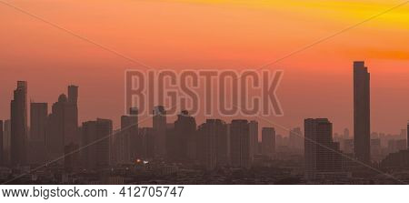Air Pollution. Smog And Fine Dust Of Pm2.5 Covered City In The Morning With Orange Sunrise Sky. City