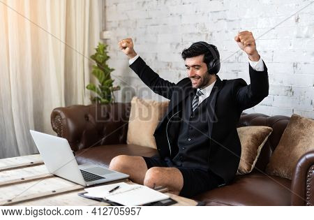 Happy Young Businessman Work From Home Looking At Laptop Excited By Good News Online, Lucky Successf