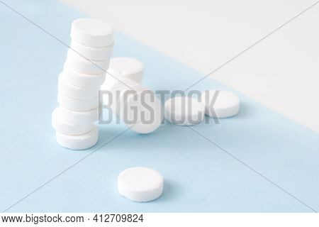A Stack Of Pills On A Blue Background. Growth Graph Made Of Stacked White Pills - Growing Market And