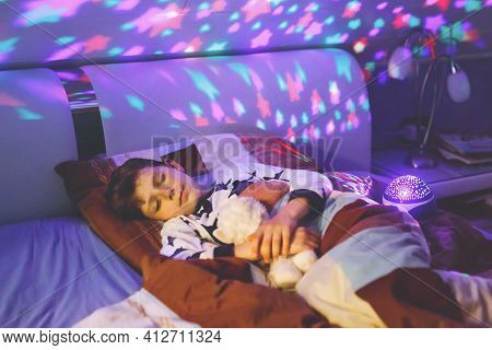 Little Kid Boy Sleeping In Bed With Colorful Lamp. School Child Dreaming And Holding Plush Toy. Kid