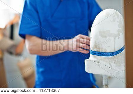 Prosthetist Man Making Prosthetic Leg While Working In Laboratory, Makes A Model Of Plaster.