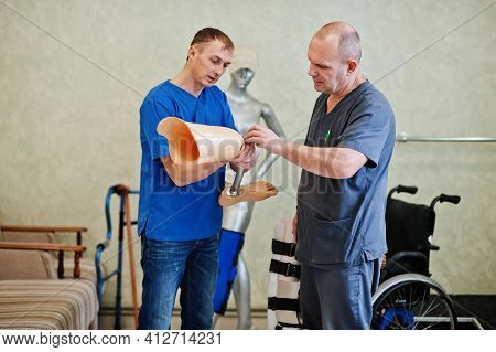 Two Prosthetist Man Workers With Prosthetic Leg Working In Laboratory.