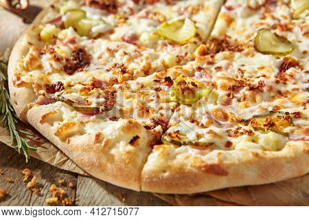 Tasty pizza with ham, gherkins, fried onions and pickle cucumber. Garnished on parchment with pizza ingredients on wooden table. Rustic style, sunlight