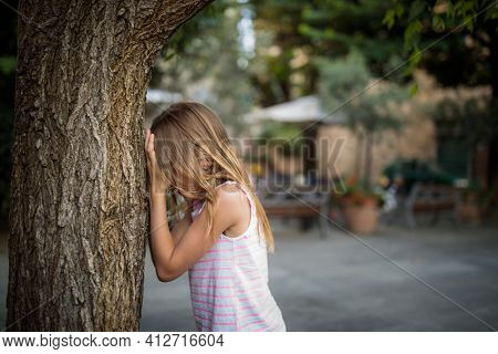 Little girl playing hide and seek with friends, counting by a tree, waiting for them to hide