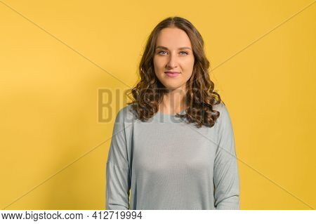 Calm And Smiling Young Blue Eyed Brunette Woman Looks At The Camera, A Beautiful Positive Curly Fema