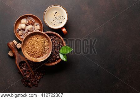 Roasted coffee beans, ground powder, brown sugar and cup of hot espresso coffee. Top view flat lay with copy space