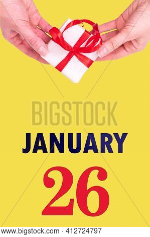 January 26th. Festive Vertical Calendar With Hands Holding White Gift Box With Red Ribbon And Calend