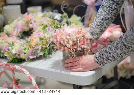 Business Owner Selling Behind Counter With Her Bouquet Of Dried Flowers At Local Market Of Craftsmen