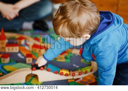 Little Toddler Boy Playing With Wooden Railway, Indoors. Happy Cute Child Moving Trains At Home Or D