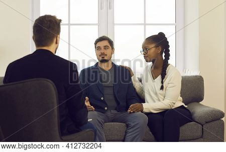 Young Interracial Spouses Talking To Man Specialist At Family Consultation