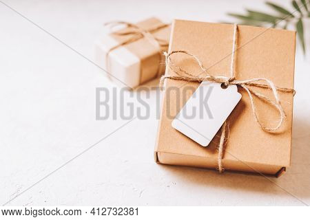 Craft Eco Gift Or Present Box With Blank Mockup Tag, Bow And On White Background. Copy Space For Tex