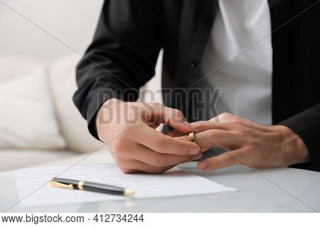 Man Taking Off Wedding Ring At Table Indoors, Closeup. Divorce Concept