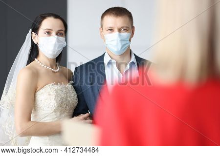 Bride And Groom Wearing Medical Protective Masks Standing In Front Of Receptionist