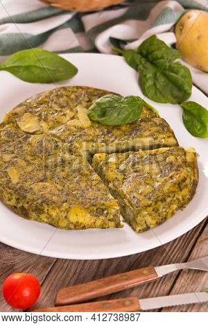 Spanish Omelette With Spinach On White Dish.