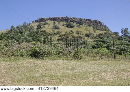 Steep Hill With Vegetation Rising From Grassy Area