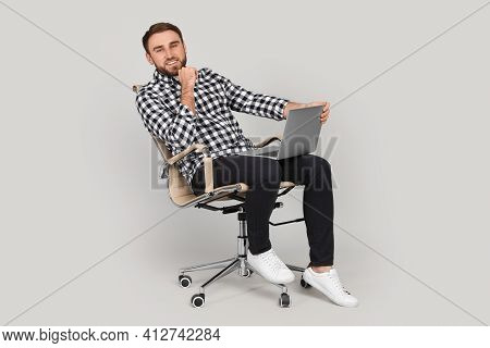 Young Man With Laptop Sitting In Comfortable Office Chair On Grey Background