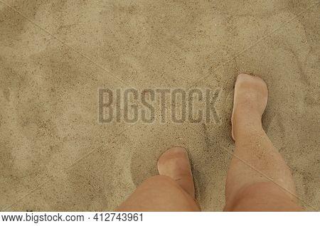 Women's Feet In The Sand On The Beach. The Feet Of A Man On A Sandy Beach. Rest On The Sandy Seashor