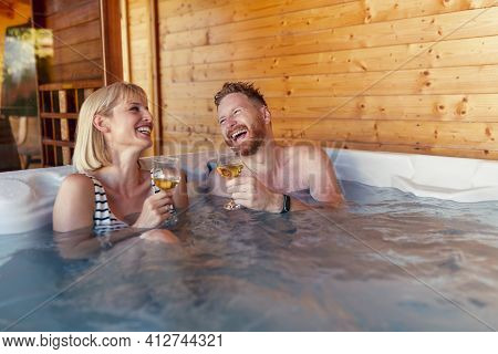 Beautiful Young Couple In Love Relaxing And Drinking Wine In A Hotel Resort Spa Center Hot Tub, Havi