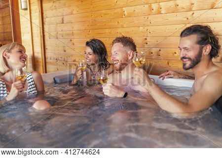 Group Of Cheerful Young Friends Relaxing In A Hotel Resort Spa Center Hot Tub, Drinking Wine And Hav