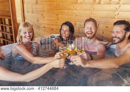 Group Of Cheerful Young Friends Relaxing In A Hotel Resort Spa Center Hot Tub, Making A Toast Raisin