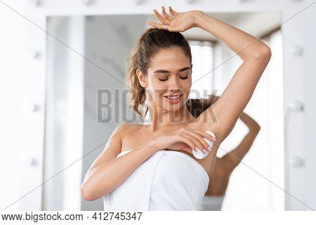Woman Applying Deodorant Antiperspirant Underarms For Sweat Protection In Bathroom