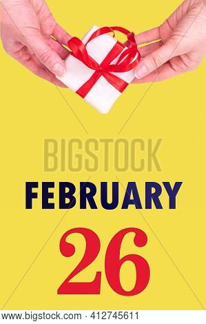 February 26th. Festive Vertical Calendar With Hands Holding White Gift Box With Red Ribbon And Calen