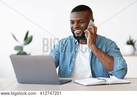 Black Male Entrepreneur Talking On Cellphone And Working On Laptop In Office