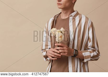 Cropped Portrait Of Feminine Young Man Holding Flowers While Standing Against Neutral Beige Backgrou