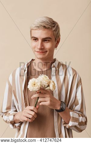 Vertical Portrait Of Feminine Blonde Man Holding Flowers And Smiling While Standing Against Neutral