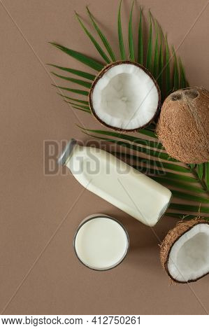 Coconut  Milk With Coconut Halves Top View On Brown Background. Coconut Vegan Milk.