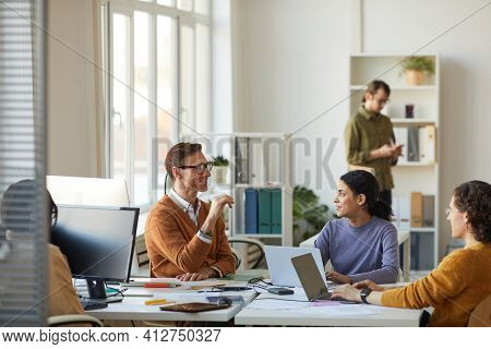 Wide Angle Portrait Of Young Business Team Discussing Startup Project While Working At Desk In White