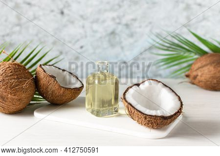 Bottle Of Coconut Oil And Fresh Coconuts With Palm Leaf On White Wooden Table. Coconut Natural Cosme