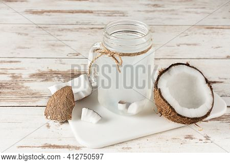 Coconut Water In A Glass Masson Jar On White Wooden Table. Fresh Detox Coconut Juice.