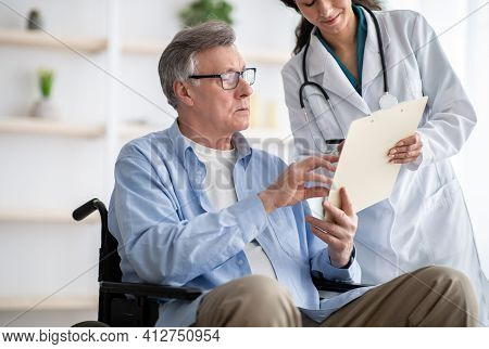 Positive Female Doctor Offering Disabled Elderly Man To Sign Insurance Contract At Home