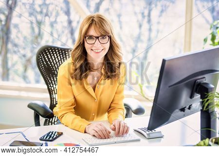 Shot Of Happy Mature Businesswoman Sitting At Office Desk While Having Video Call In The Office.