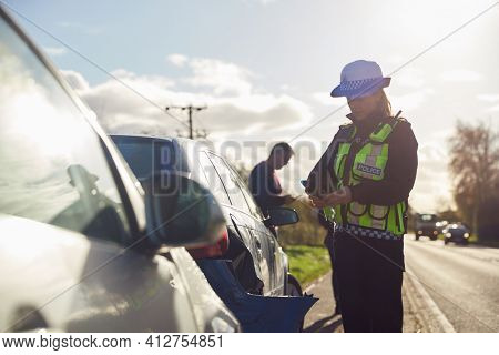 Female Traffic Police Officer Taking Photos On Mobile Phone At Road Traffic Accident