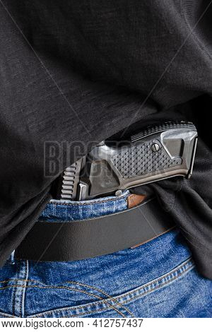 Hided Handgun Under The Denim Belt. A Person Is Hiding A Handgun Under The Denim Belt.