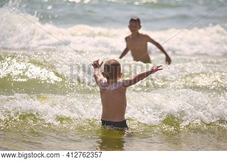 Child Swims In The Sea Waves On The Beach 2021
