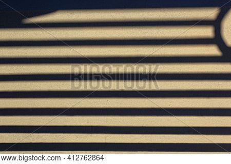 The Shadow From Antique Ornate Metal Fence On Beige Stucco Wall Of Old Building. Abstract Background