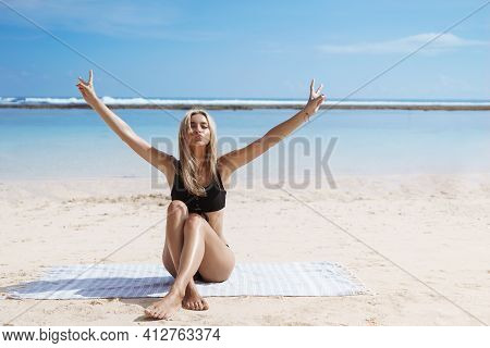 Woman In Bikini Sitting On Tropical Beach And Raising Hands Free. Happy Female Tourist Relaxing On S
