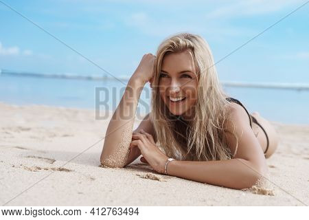 Happy Woman Sunbathing On Tropical Beach In Bikini. Smiling Female Tourist Lying On Sand Near Ocean