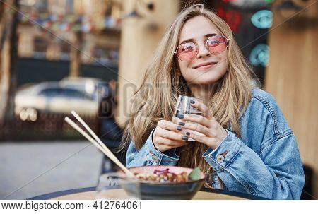 Happy Woman Eating Outdoors Chinese Asian Food, Sitting On Street Table And Drinking Water, Wearing